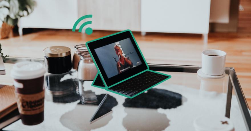 Fotografi av ett glasbord med en dator, takeawaykopp och en kopp kaffe. Några ljus skymtas i bakgrunden. Den finns en grön wifi-symbol ovanför datorn.