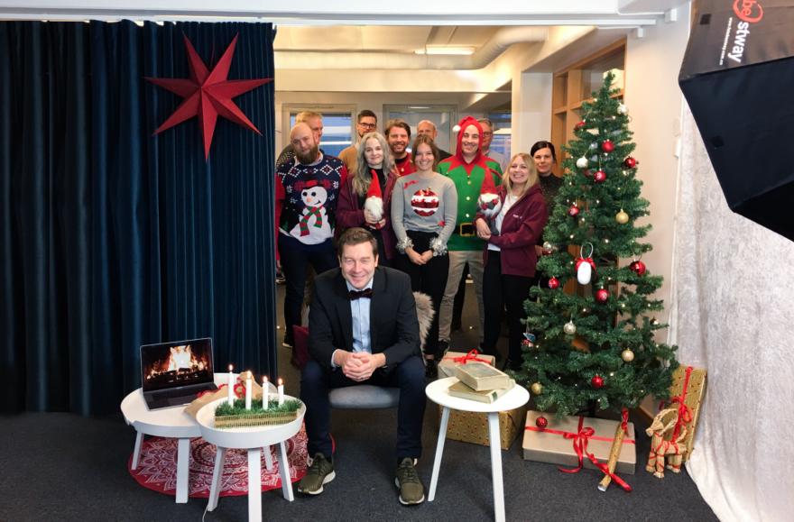 Fotografi av Daniel Krook, VD på Bredband2 och ett gäng medarbetare i bakgrunden iklädda jultröjor. På bild syns även julgran, julstjärna och adventsljusstake.