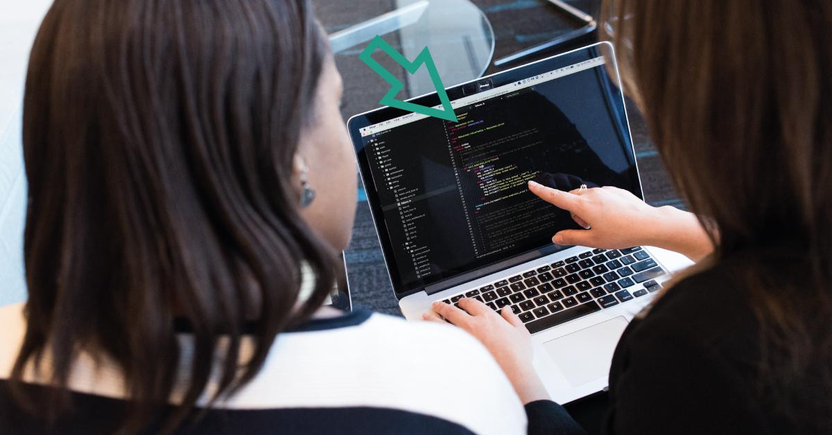 Fotografi av två kvinnor som sitter framför en dator varav den ena pekar på skärmen. Bilden anspelar på kvinnor och it.
