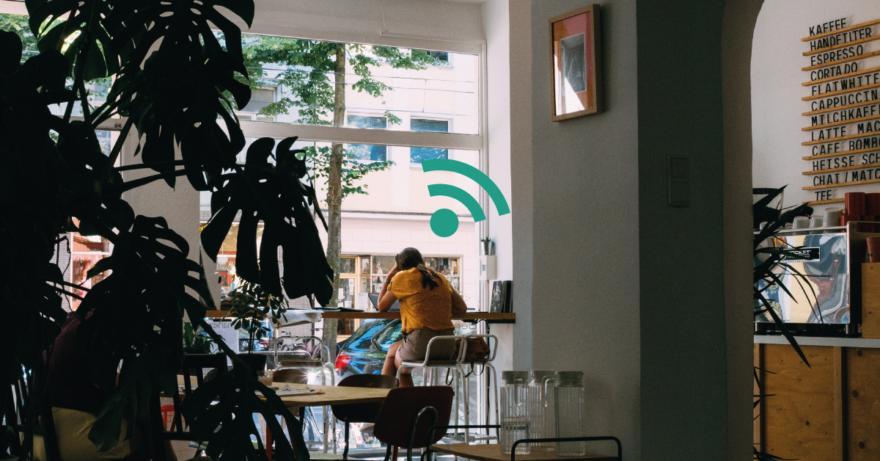 Fotografi av student som sitter och surfar på ett café med en stor växt i förgrunden. Anspelar på säkerhetstips till dig som studerar.