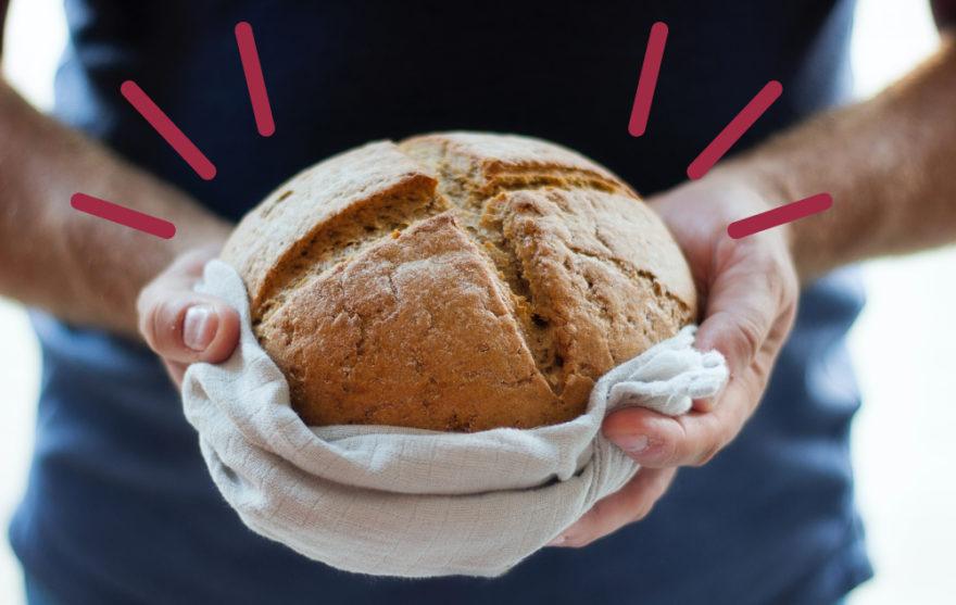 Bild på en person som håller i en brödlimpa.