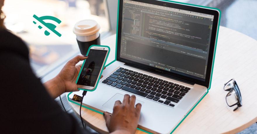 En person som sitter vid datorn och surfar med en mobiltelefon i vänster hand.