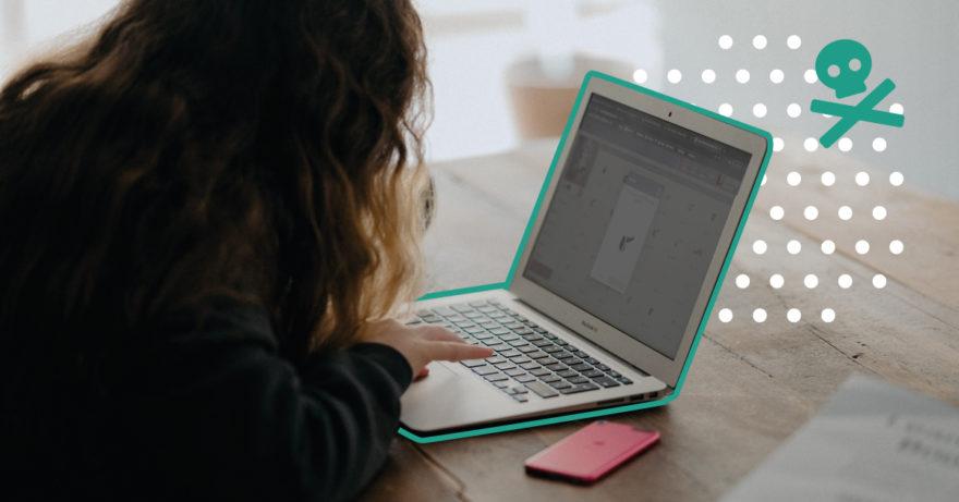 En kvinna som sitter framåtlutad vid sin dator. Till höger om datorn syns en döskalle.