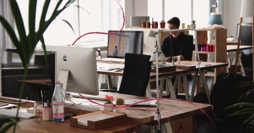 Foto på kontor med datorer, en man sitter med sin dator i bakgrunden