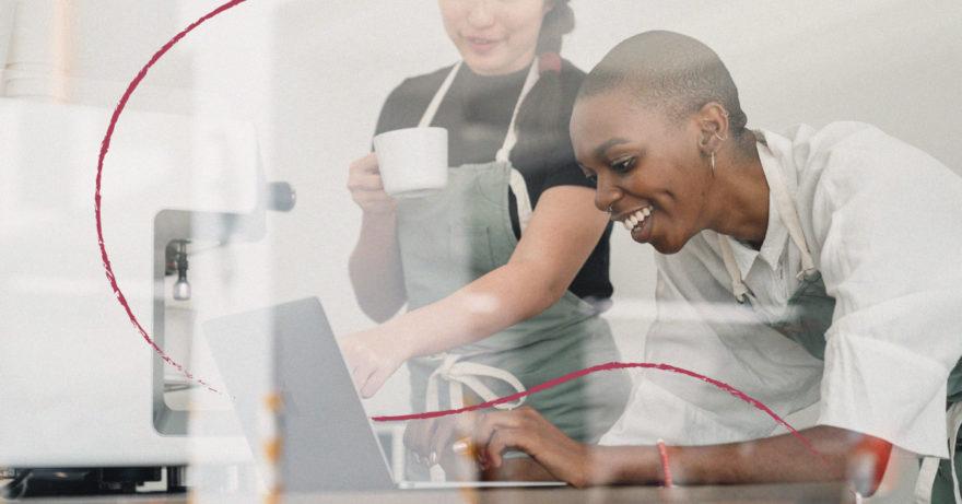 Två kvinnor med förkläde tittar på laptop