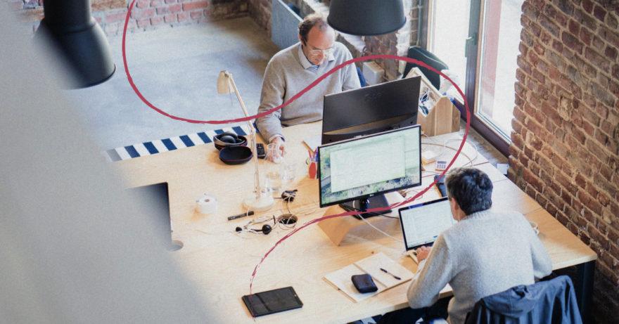 Foto ovanifrån på två män som arbetar på ett kontor med sina datorer